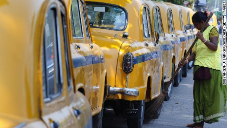 A street cleaner sweeps the road next to parked Ambassador taxis in Kolkata.