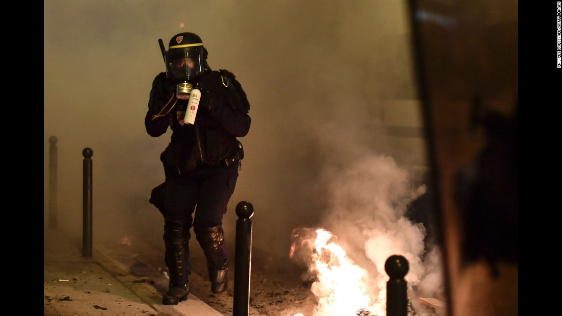 "A police officer holds a tear-gas canister during <a href=""http://www.cnn.com/2017/02/16/europe/paris-anti-police-protests/"" target=""_blank"">anti-police protests in Paris</a> on Wednesday, February 15. Two hundred people gathered in the neighborhood of Barbes, near the Gare du Nord train station, to protest the alleged rape of a 22-year-old black man by police."