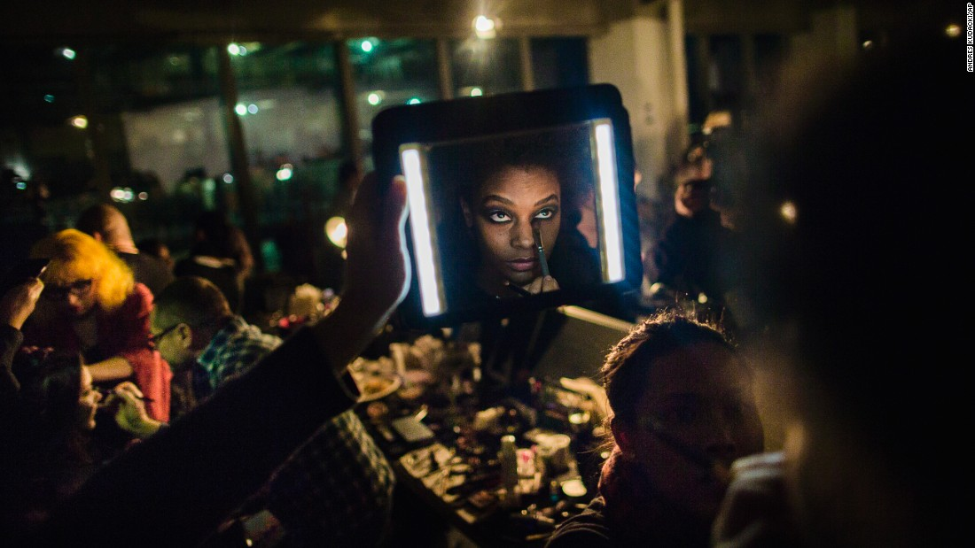 A makeup artist works on a model as an assistant lights the model's face during a fashion show in New York on Tuesday, February 14.