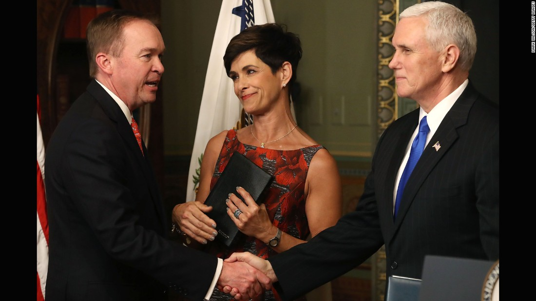 Vice President Mike Pence, right, shakes hands with Mick Mulvaney after swearing him in as the new director of the Office of Management and Budget on Thursday, February 16. Mulvaney's wife, Pam, looks on. Mulvaney had been a congressman since 2011.