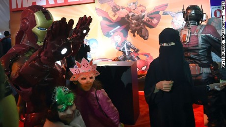 "A Saudi woman looks on as children pose for a photo with a man dressed up as ""Iron Man"" during the country's first ever Comic-Con event in the coastal city of Jeddah on February 16, 2017. The three-day festival of anime, pop art, video gaming and film-related events is part of a government initiative to bring more entertainment to Saudi Arabia which bans alcohol, public cinemas and theatre. / AFP / FAYEZ NURELDINE        (Photo credit should read FAYEZ NURELDINE/AFP/Getty Images)"
