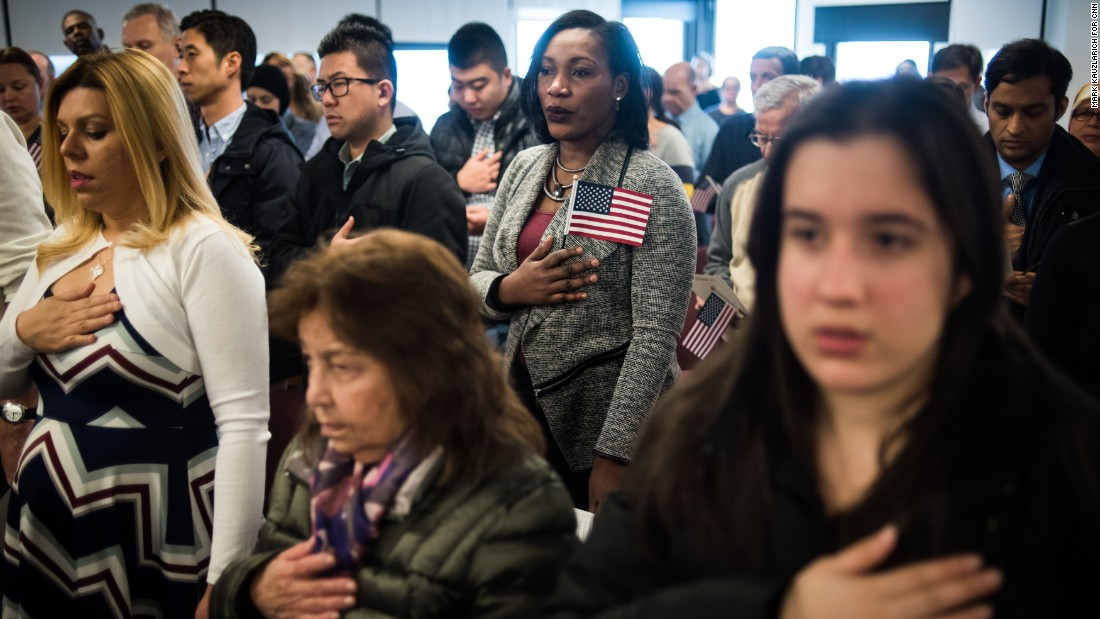 People listen to the national anthem during a naturalization ceremony in Newark, New Jersey, on Thursday, February 16.