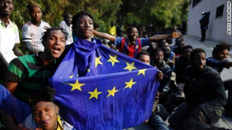 A migrant holding a European Union flag sits on the ground with others on Friday, February 17, after storming a fence to enter the Spanish enclave of Ceuta.
