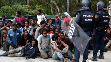 Migrants sit on the ground next to Spanish police officers after crossing into Ceuta.