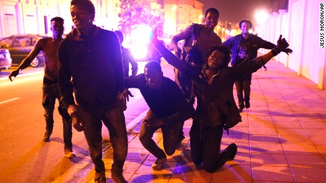 Migrants celebrate after storming the fence and entering the Spanish enclave of Ceuta.