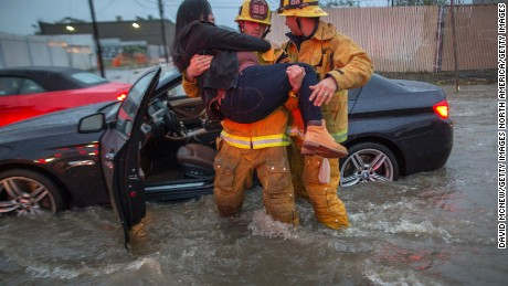 SUN VALLEY, CA - FEBRUARY 17:  A firefighter carries a woman from her car after it was caught in street flooding as a powerful storm moves across Southern California on February 17, 2017 in Sun Valley, California. After years of severe drought, heavy winter rains have come to the state, and with them, the issuance of flash flood watches in Santa Barbara, Ventura and Los Angeles counties, and the evacuation of hundreds of residents from Duarte, California for fear of flash flooding from areas denuded by a wildfire last year.   (Photo by David McNew/Getty Images)