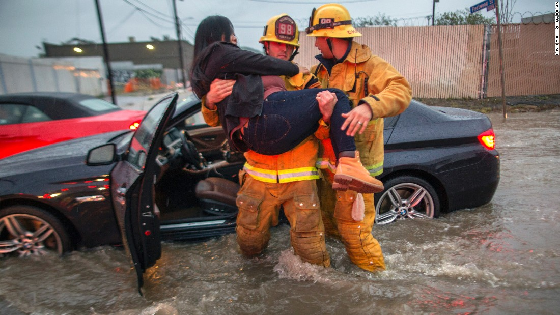 A firefighter carries a woman after floodwaters engulfed her car on a street in Los Angeles' Sun Valley neighborhood on February 17.