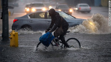 A bicyclist rides along a flooded street as a powerful storm moves across Southern California on February 17, 2017 in Sun Valley, California. After years of severe drought, heavy winter rains have come to the state, and with them, the issuance of flash flood watches in Santa Barbara, Ventura and Los Angeles counties, and the evacuation of hundreds of residents from Duarte, California for fear of flash flooding from areas denuded by a wildfire last year.
