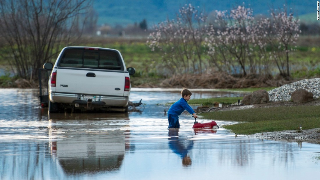 Barr Torrens plays in flooded neighborhood streets after a deluge of rain and runoff flooded much of Maxwell on February 18.