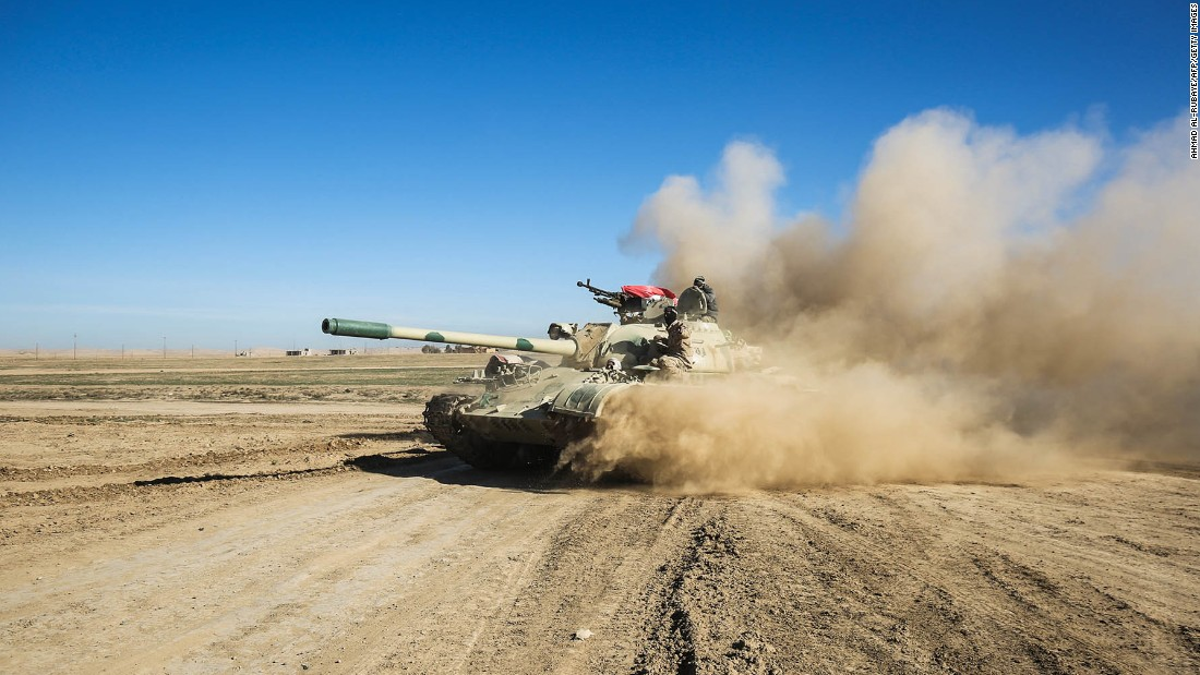 "Iraqi forces advance in tanks and armored vehicles toward the village of Sheikh Younis, south of Mosul, on Sunday, February 19. Prime Minister Haider al-Abadi described the operation as a ""new dawn"" in the liberation of Mosul."