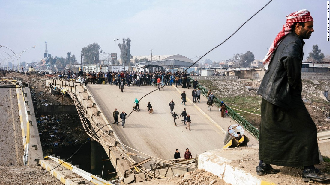 Mosul residents cross a damaged bridge in the al-Sukkar neighborhood on Saturday, January 21.