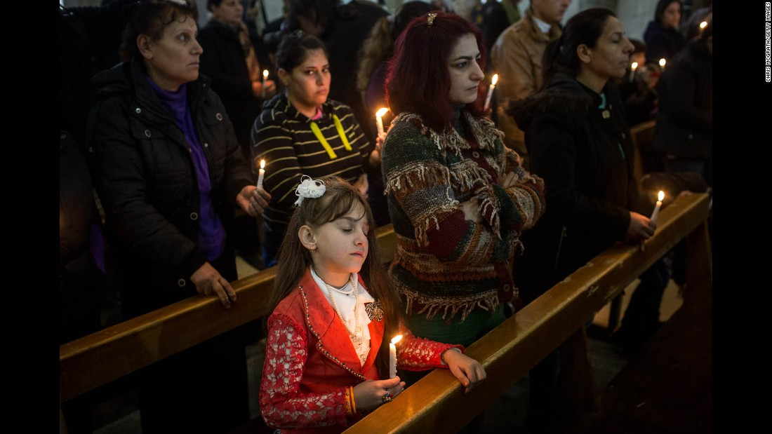 A young girl takes part in a Christmas Day Mass at a church in the predominantly Christian town of Qaraqosh. The area's churches were heavily damaged by ISIS militants before the town was freed by Iraqi forces during the Mosul offensive.