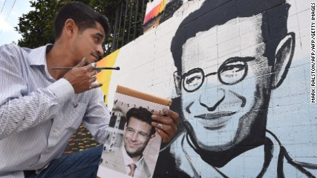 Artist Levi Ponce poses with his Memorial Day mural project of murdered journalist Daniel Pearl, near his old neigborhood in Los Angeles, California on May 23, 2015.  Pearl was a Wall Street Journal reporter who was kidnapped and murdered by a terrorist group in Pakistan in 2002 while doing an investigative story. The artist is working with students from the Daniel Pearl High School and LAPD West Valley Police cadets on the project.        AFP PHOTO/MARK RALSTON        (Photo credit should read MARK RALSTON/AFP/Getty Images)