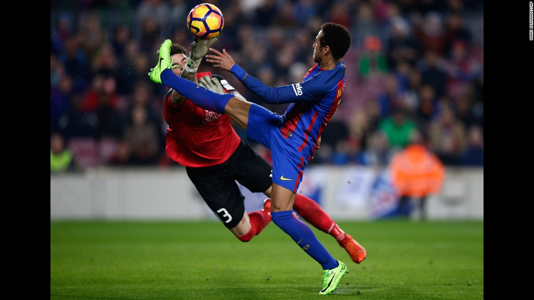 Leganes goalkeeper Iago Herrein swats at the ball near Barcelona forward Neymar during a Spanish league match in Barcelona on Sunday, February 19.