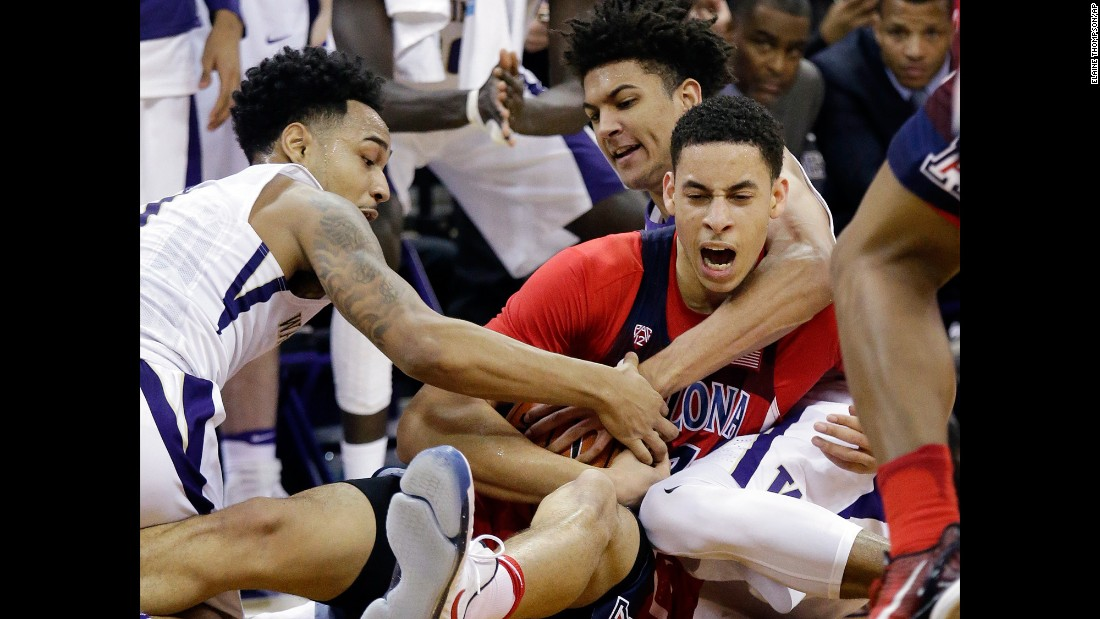 Arizona's Chance Comanche is swarmed by Washington players as they compete for a loose ball in Seattle on Saturday, February 18.