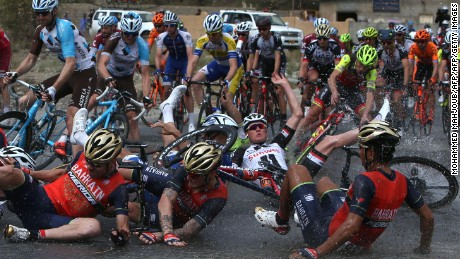 TOPSHOT - Riders fall to the ground during the fifth stage of the 2017 cycling Tour of Oman between Samail to Jebel Akhdhar (Green Mountain), on February 18, 2017. / AFP / MOHAMMED MAHJOUB        (Photo credit should read MOHAMMED MAHJOUB/AFP/Getty Images)