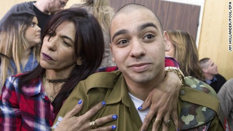 epa05806304 Israeli soldier Elor Azaria (R) is embraced by his mother at the start of his sentencing hearing in a Israel military court in Tel Aviv, 21 February 2017. Elor Azaria was convicted by Israeli military prosecutors of killing a Palestinian attacker who was wounded and already laying on the ground after a knife attack on Israeli soldiers in Hebron on 24 March 2016.  EPA/JIM HOLLANDER / POOL
