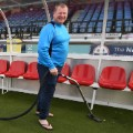 Wayne Shaw vacuums Arsenal's dugout before the match between Sutton United's game Monday.