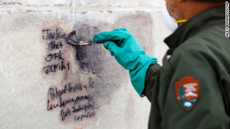 A U.S. Park Service employee works to clean graffiti off of the Washington Monument, Tuesday, February 21 in Washington.