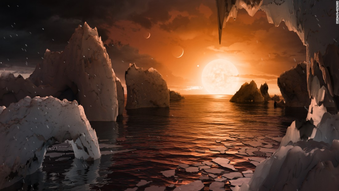 An artist's concept image of the surface of the exoplanet TRAPPIST-1f. Of the seven exoplanets discovered orbiting the ultracool dwarf star TRAPPIST-1, this one may be the most suitable for life. It is similar in size to Earth, is a little cooler than Earth's temperature and is in the habitable zone of the star, meaning liquid water (and even oceans) could be on the surface. The proximity of the star gives the sky a salmon hue, and the other planets are so close that they appear in the sky, much like our own moon.