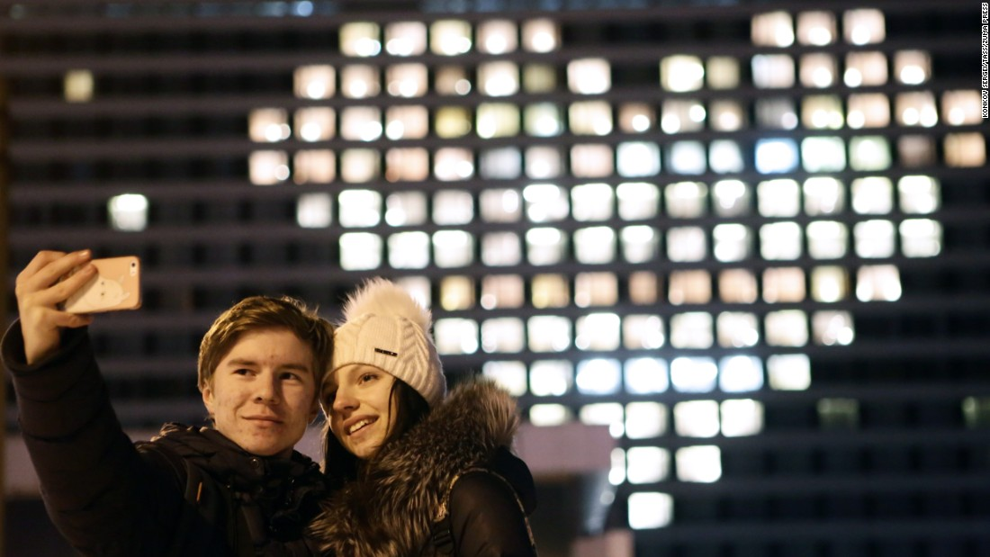 A couple takes a Valentine's Day selfie in front of a hotel in St. Petersburg, Russia.