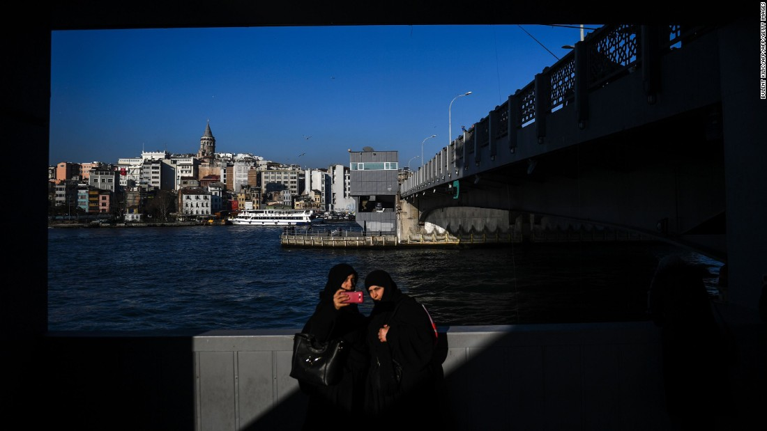 Two women take a photo at the Galata Bridge in Istanbul on Thursday, February 2.