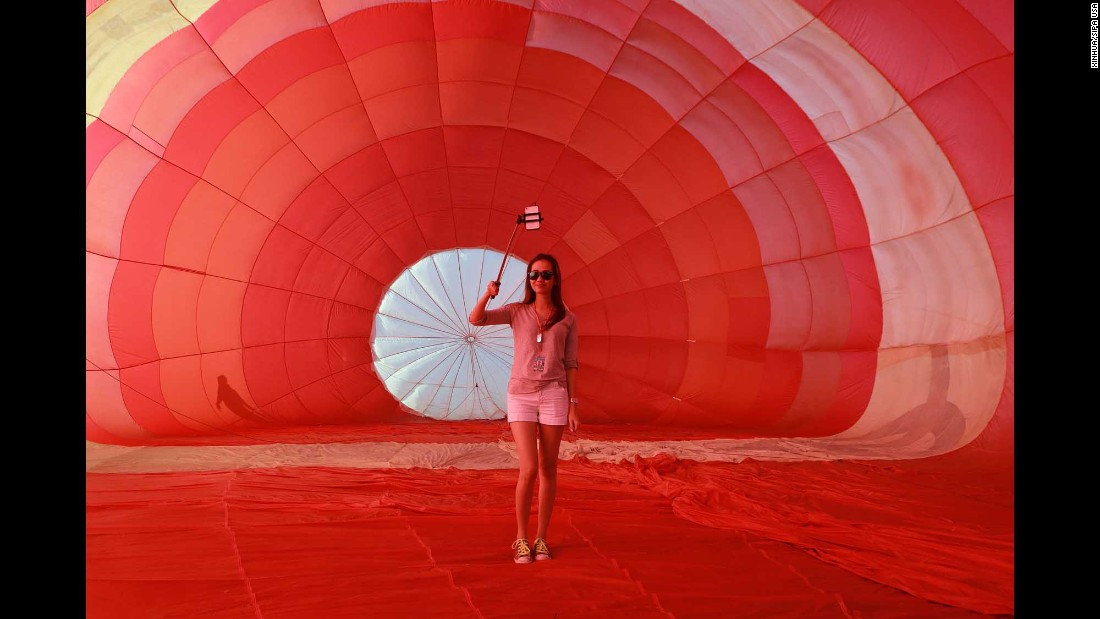 A woman uses a selfie stick Thursday, February 9, during the Philippine International Hot Air Balloon Fiesta.