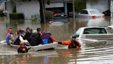 Rescue crews take out residents from a flooded neighborhood Tuesday, Feb. 21, 2017, in San Jose, Calif. Rescuers chest-deep in water steered boats carrying dozens of people, some with babies and pets, from a San Jose neighborhood inundated by water from an overflowing creek Tuesday. (AP Photo/Marcio Jose Sanchez