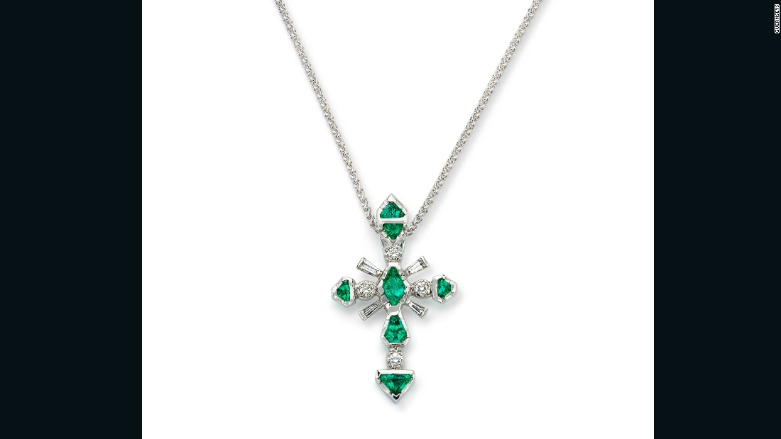 Seven kite-cut Colombian emeralds and diamonds, set in platinum, form a cross.