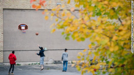 Refugees play basketball outside a shelter while waiting to find out if they will be granted asylum.