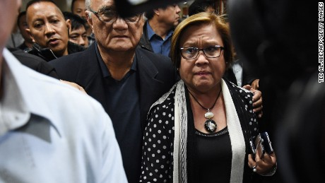 Philippine Senator Leila De Lima (centre R), a top critic of President Rodrigo Duterte, is escorted by security personnel as she walks to a press conference in the senate in Manila on February 23, 2017, as she awaits the warrant of arrest to be served. An arrest warrant was issued February 23, for the highest-profile opponent of Philippine President Rodrigo Duterte's brutal war on drugs, outraging her supporters who said the move was aimed at silencing her. Senator Leila de Lima, 57, a lawyer who has spent nearly a decade trying to link Duterte to death squads that have allegedly killed thousands of people, faces drug trafficking charges that could see her jailed for life. / AFP / TED ALJIBE