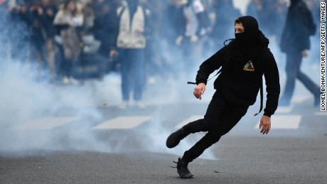 "A young man runs away from tear gas launched  by riot police during a protest of students against police brutality, following the alleged rape of Theo, next to the ""Lycee Voltaire"" secondary school in Paris, on February 23, 2017. / AFP / Lionel BONAVENTURE        (Photo credit should read LIONEL BONAVENTURE/AFP/Getty Images)"