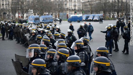 Riot police forces stand guard.