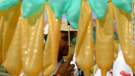 An Indian volunteer holds an umbrella decorated with condoms during an event to mark International Condom Day in New Delhi on February 13, 2017.
