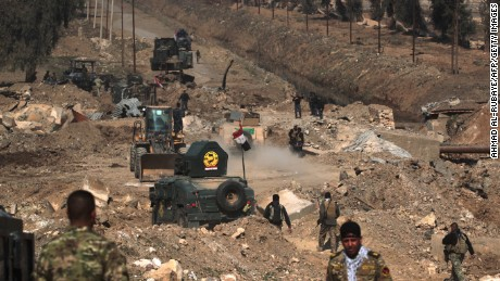 Iraqi forces advance on February 23, 2017 as they enter Mosul airport on the southern edge of the jihadist stronghold for the first time since the Islamic State group overran the region in 2014.Backed by jets, gunships and drones, forces blitzed their way across open areas south of Mosul and entered the airport compound, apparently meeting limited resistance but strafing the area for suspected snipers.