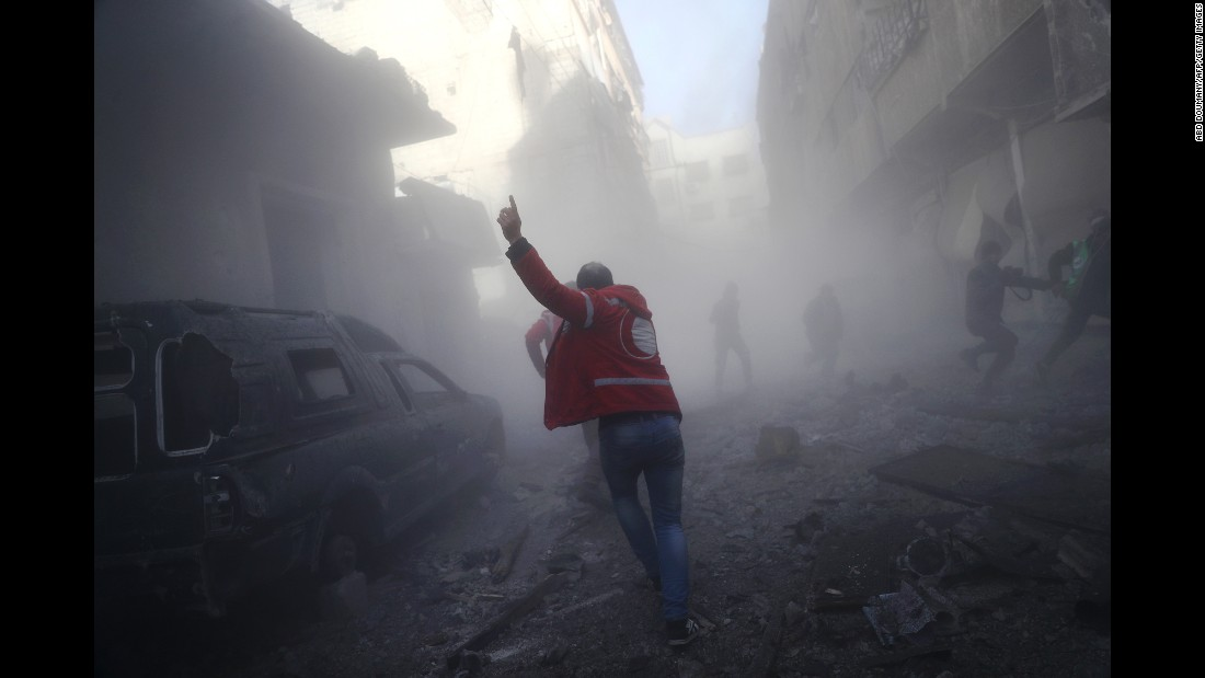 A member of the Syrian Arab Red Crescent searches for victims after an airstrike on the rebel-held town of Douma, Syria, on Sunday, February 19.