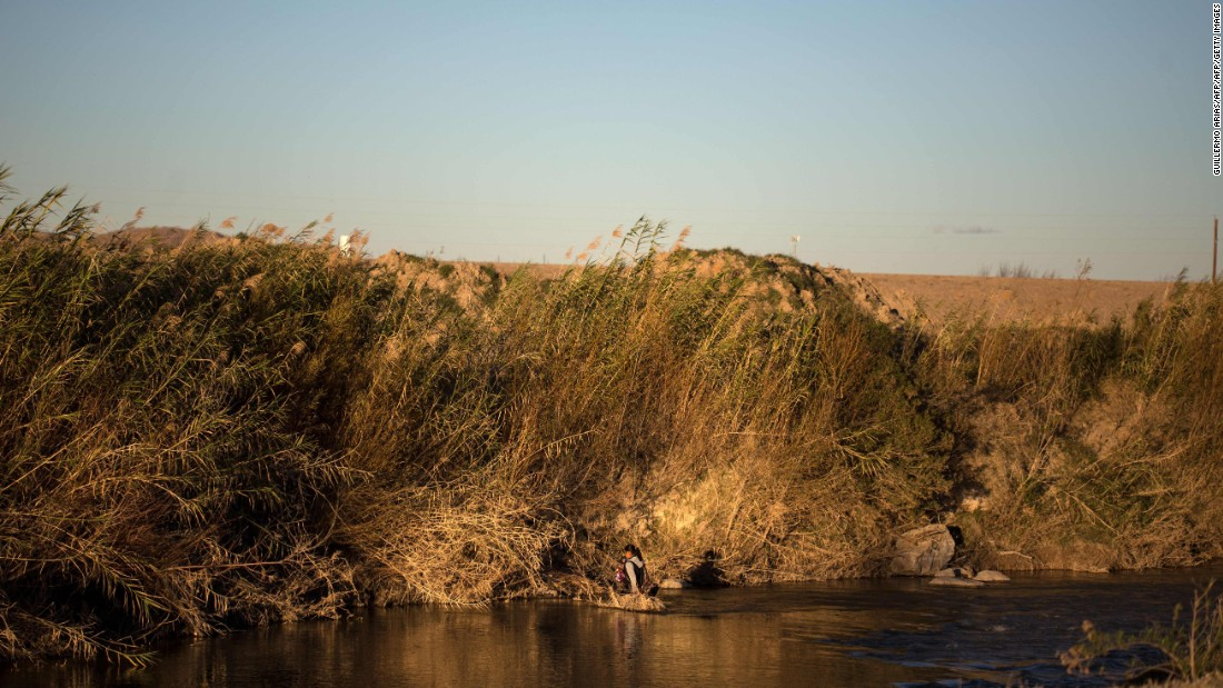 A woman crosses the Rio Bravo with a baby in her arms at the US-Mexico border in Ojinaga, Mexico, on Monday, February 20.