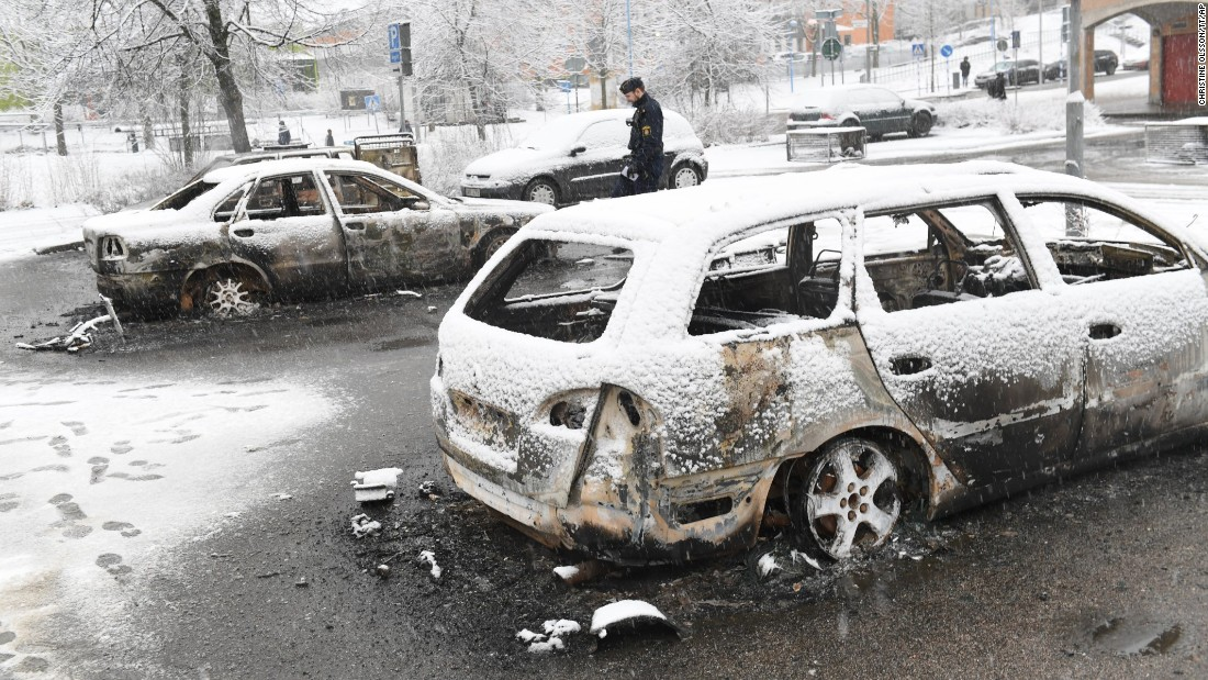 "A police officer investigates a burned-out car in Stockholm, Sweden, on Tuesday, February 21. <a href=""http://www.cnn.com/2017/02/21/europe/sweden-stockholm-riots/"" target=""_blank"">Riots broke out</a> in a predominantly immigrant neighborhood the night before, as residents clashed with police officers and set vehicles on fire, Swedish police said. Stockholm regional police chief Ulf Johansson said the clashes may have been a result of their ""increased pressure on criminals in the area."""