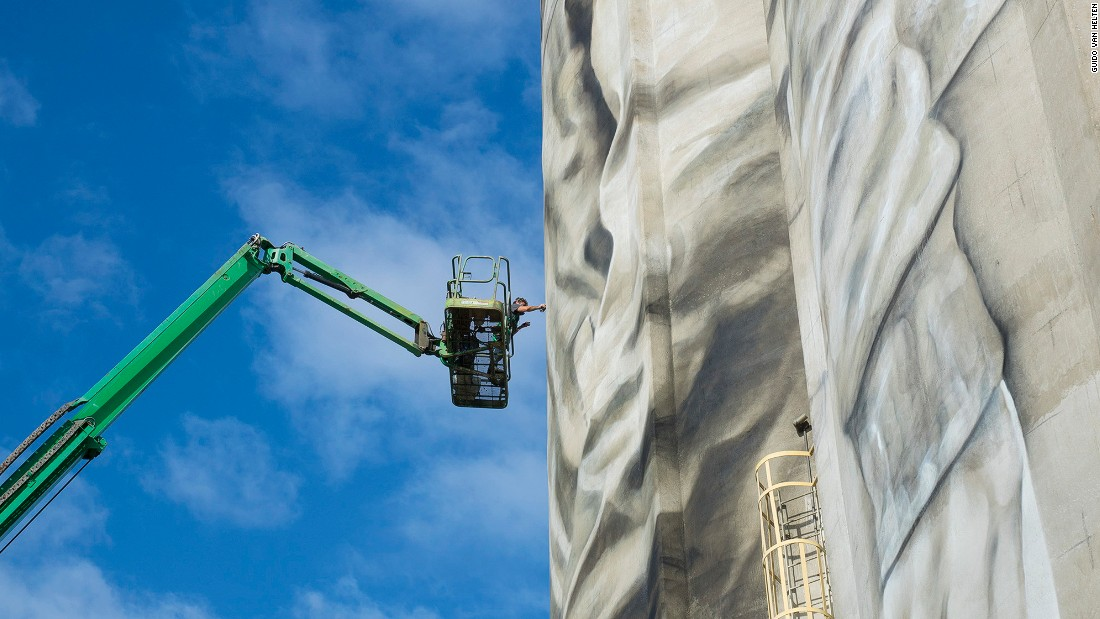 "Van Helten uses a cherry picker to paint his silo mural entitled ""Unity"" in Jacksonville, Florida, US."