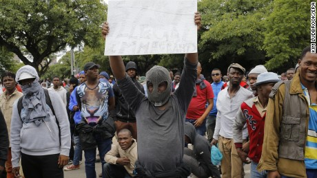 A South African holds a placard calling for foreign residents to leave the city during a xenophobic march through the streets of Pretoria, South Africa, 24 February 2017.