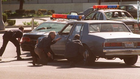 Los Angeles police officers take cover behind police cars, two with windows shattered from gunfire, outside a Bank of America branch in the North Hollywood section of Los Angeles Friday, Feb. 28, 1997. Two robbers were killed and several people injured in the shootout during the bungled robbery. (AP Photo/Mike Meadows)