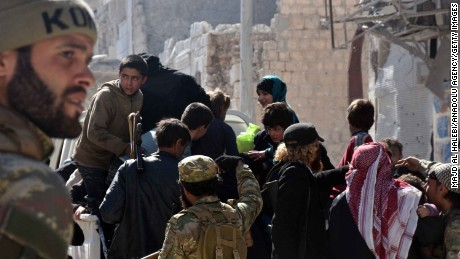 Members of the Free Syrian Army escort civilians Thursday after taking the center of al-Bab from ISIS.