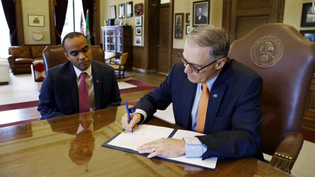 Washington Gov. Jay Inslee -- at right, next to general counsel Nick Brown -- signs an executive order Thursday, February 23, to restrict state workers and agencies from enforcing President Trump's immigration policies. Inslee has been outspoken about the Trump administration, and he said his order reaffirms the state's commitment to tolerance.