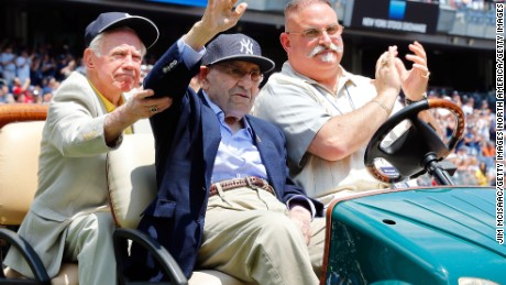 With help from former teammate New York Yankee Whitey Ford (left), former New York Yankee Yogi Berra (center) is introduced during the team's Old Timers Day in 2014.