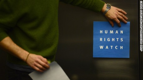 A man puts the logo of US-based rights group Human Rights Watch on the wall as he prepares a room before a press conference on January 21, 2014 in Berlin.