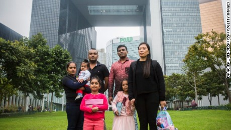 Sri Lankan refugee Supun Thilina Kellapatha (3rd L), 32, his partner Nadeeka (L), 33, with their baby boy Dinath, daughter Sethumdi, 5, Sri Lankan refugee Ajith Puspa (3rd R), 45, and Filipino refugee Vanessa Rodel (R), 40, with her daughter Keana, 5, pose for a photo in front of the government buildings of Hong Kong on February 23, 2017, after attending a press conference where allegations were discussed about the refugees who provided accommodation to Edward Snowden while he was in the city were being searched for by the Sri Lankan Criminal Investigation Division (CID) in Hong Kong. / AFP / ISAAC LAWRENCE        (Photo credit should read ISAAC LAWRENCE/AFP/Getty Images)