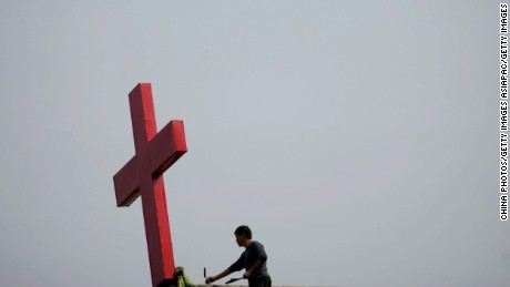 SHOUXIAN COUNTY, CHINA - OCTOBER 3: (CHINA OUT) A worker repairs the base of the cross on roof of a Christian church on October 3, 2006 in Shouxian County of Anhui Province, China. The renovation project will be completed before Christmas Day of 2006 after four months of repair work and reportedly cost 400,000 Yuan (about USD 50,484). The palace-style church was built in 1922 by an American missionary and covered an area of 398 square meters. Accoreding to State Media released on August 1st, China has more than 15-million Christians with 25,000 meeting places and 12,000 churches across China. (Photo by China Photos/Getty Images)