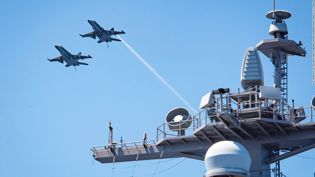 Two F/A-18E Super Hornets fly over the aircraft carrier USS Carl Vinson  on February 22.