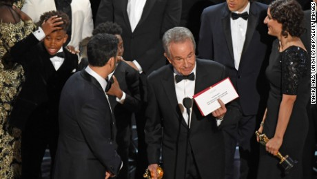 "The cast of ""Moonlight"" and ""La La Land"" appear on stage as presenter Warren Beatty shows the winner's envelope for Best Movie ""Moonlight"" on stage."
