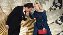 Javier Bardem kisses Meryl Streep's hand as they present an award.